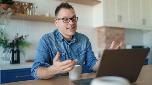 man-smiling-infront-of-laptop